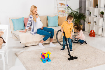 happy pregnant woman looking at adorable little children cleaning room with vacuum cleaner at home