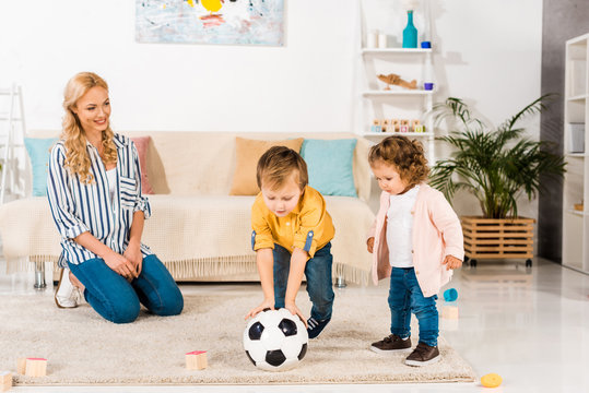 smiling mother looking at cute little children playing with soccer ball at home