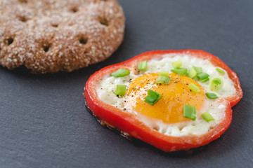 Fried eggs with red sweet pepper and chives on a black slate background.