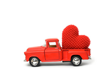 Red toy car delivering red heart for valentine's day on white background