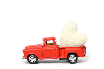 Red toy car delivering white heart for Valentine's day on white background