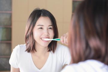 Young woman brushing her teeth at mirror. After awakening