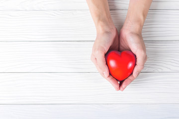 Red heart in hands on white wooden background.