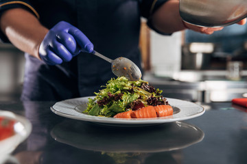 cropped shot of chef pouring sauce onto salad from spoon