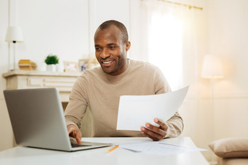 Self-employed. Handsome cheerful dark-eyed bearded afro-american man smiling and working on the laptop and holding a sheet of paper while sitting at the table