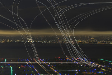 Light paintings over illuminated airport by river in city at night