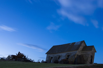 Low angle view of abandoned house on field against blue sky at night