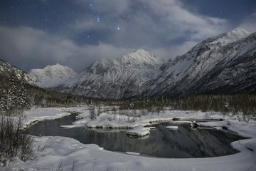 Scenic view of frozen lake by snowcapped mountain against cloudy sky