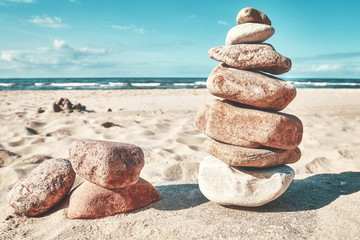 Retro toned picture of a stone stack on a beach, zen like natural background.
