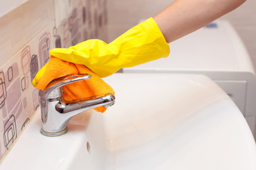 Female hands with yellow rubber protective gloves cleaning water tap with orange cloth.