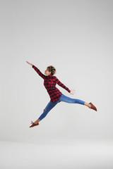 Sporty girl doing splits in the air at studio