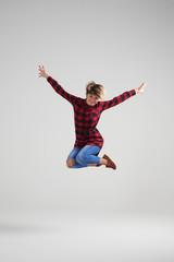 Playful young woman in casual clothes jumping at studio