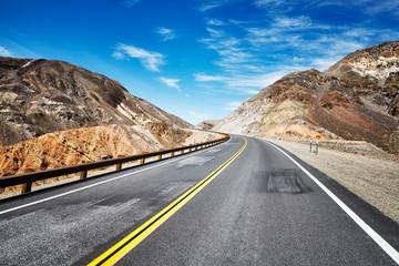 Empty highway in deserted mountainous terrain, travel concept, USA.