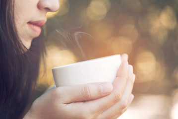 Young woman drinking coffee in the sun, outdoor in sunlight light, enjoying her morning coffee.
