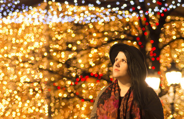Celebration concept - Merry Christmas and happy New Year - Portrait of an attractive obese woman outdoor - night bokeh lights background