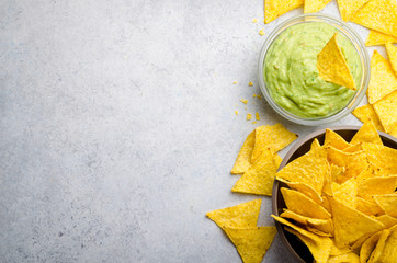 Traditional mexican homemade guacamole sauce in a glass bowl and