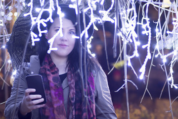 Celebration concept - Merry Christmas and happy New Year - Young beautiful girl holding a touchscreen phone texting