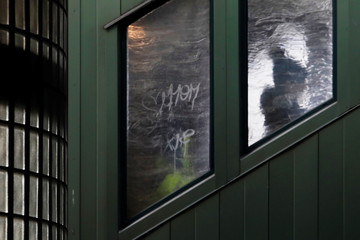 A woman is seen in silhouette through an ice covered window of a subway staircase in Queens, New York