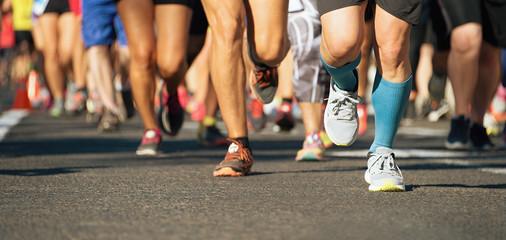 Marathon running race in the light of evening,running on city road detail on legs