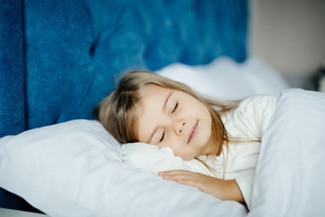 Close-up portrait of beautiful little kid lying on bed with hand under pillow, looking at camera at home