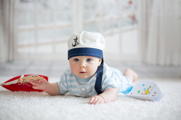Little baby boy, playing wtih little boat and little fish at home