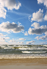 Sea waves and blue cloudy sky