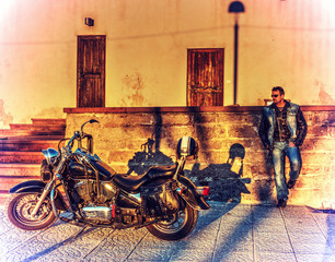 Biker standing by a classic motorycle at sunset