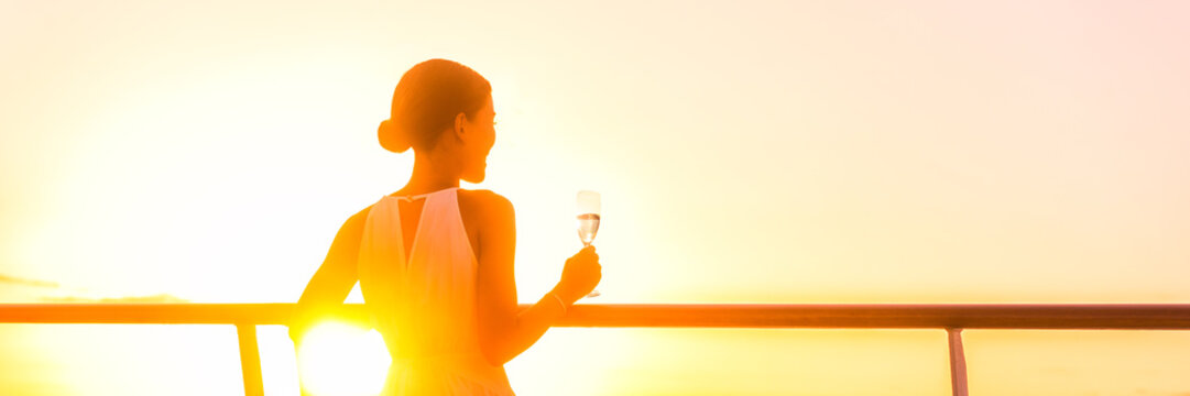 Luxury cruise ship travel elegant woman drinking champagne white wine glass watching sunset from outdoor deck or suite balcony. Europe or Caribbean cruising holiday. Banner panorama.