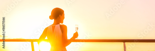 Wall mural Luxury cruise ship travel elegant woman drinking champagne white wine glass watching sunset from outdoor deck or suite balcony. Europe or Caribbean cruising holiday. Banner panorama.