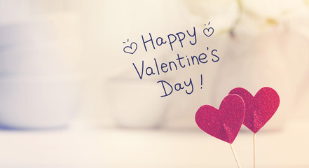 Valentines Day message with small red hearts with white dishes