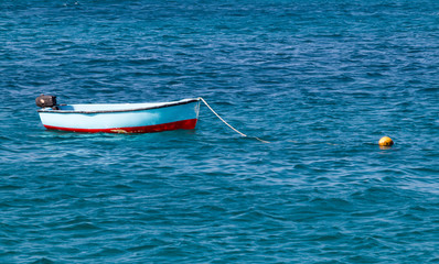 A single small blue and red wooden traditional fishing boat moored up in the blue sea in Santa Maria, Sal, Cabo Verde Islands.