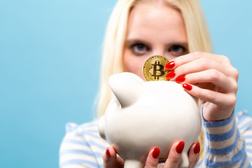 Woman with bitcoin and a piggy bank on ablue background