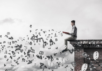 Man on roof edge reading book and symbols flying around