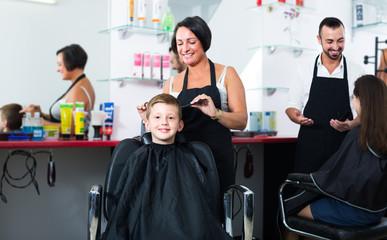 hairdresser cutting hair of boy