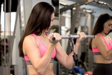 Fit woman with long dark hair working out in a gym lifting weights by the mirror