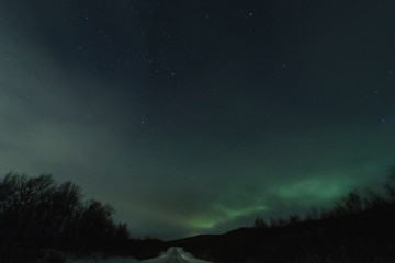 Northen lights in green stars and borealis in an show with a road lit up