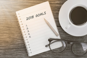 2018 Goals concept on notebook with glasses, pencil and coffee cup on wooden table.