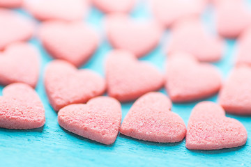 Small Pink Sugar Candy Sprinkles Spilled Scattered on Light Blue Background. Selective Focus. Pattern Template for Valentine Mother's Day Birthday Greeting Card. Wallpaper Website Banner.