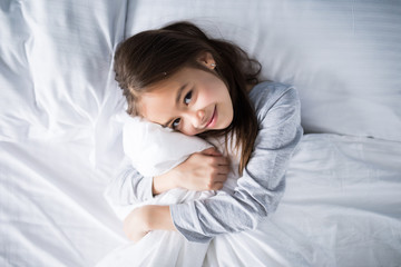 Top view portrait of a cute little girl hugging blanket while lying in bed in the morning