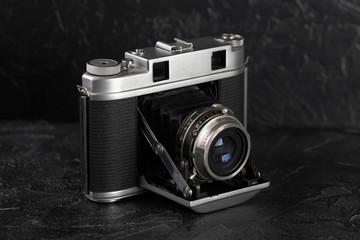 The vintage medium format film camera on black cement background.
