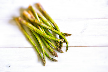 Bunch of fresh green asparagus over white wooden table