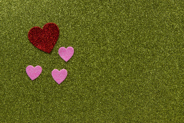 Red and pink sparkly hearts on green background with copy space