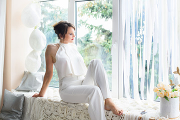 A beautiful and young girl in a white living room at home. A woman symbolizes beauty, youth, love and health