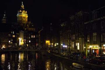Panorama of an Amsterdam canal at night with the lights of the buildings reflected on the water.