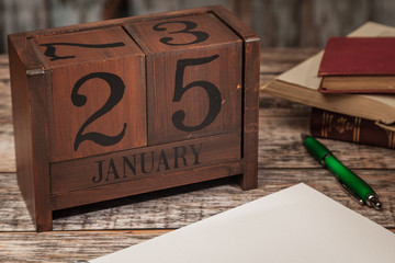 Perpetual Calendar in desk scene with blank diary page, January 25th