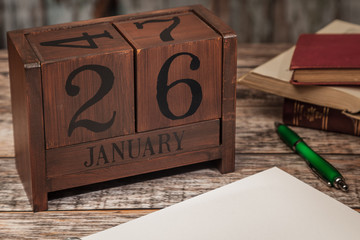 Perpetual Calendar in desk scene with blank diary page, January 26th