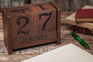 Perpetual Calendar in desk scene with blank diary page, January 27th