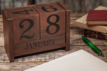 Perpetual Calendar in desk scene with blank diary page, January 28th