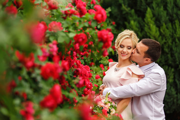 Beautiful couple in love at valentines day. Honeymoon concept. Hug in red flowers