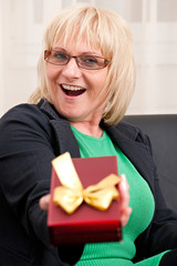 Attractive mature woman holding a gift box and smiling happily